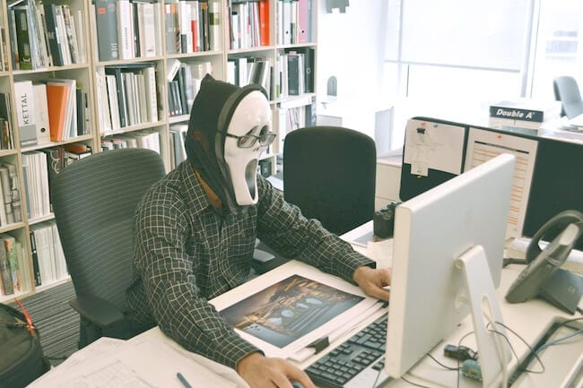 man in mask at desk employee review